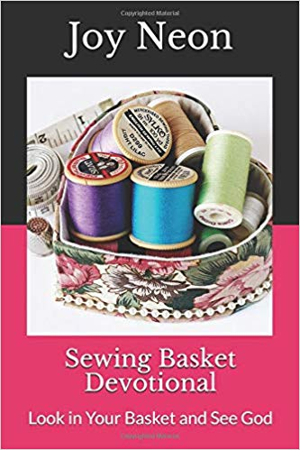 Sewing basket with spools of thread and other sewing items in a heart-shaped tin.