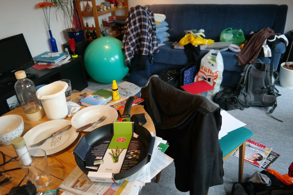Clutter in a room with clothes, food and various items strewn over a table, chair, couch and the floor.